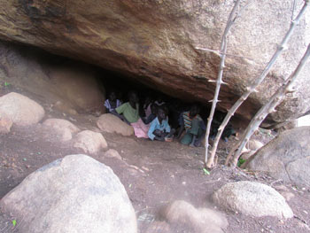 Children hiding under rocks