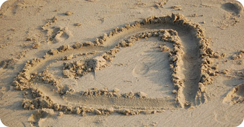 Is God's love His defining attribute? // heart in sand